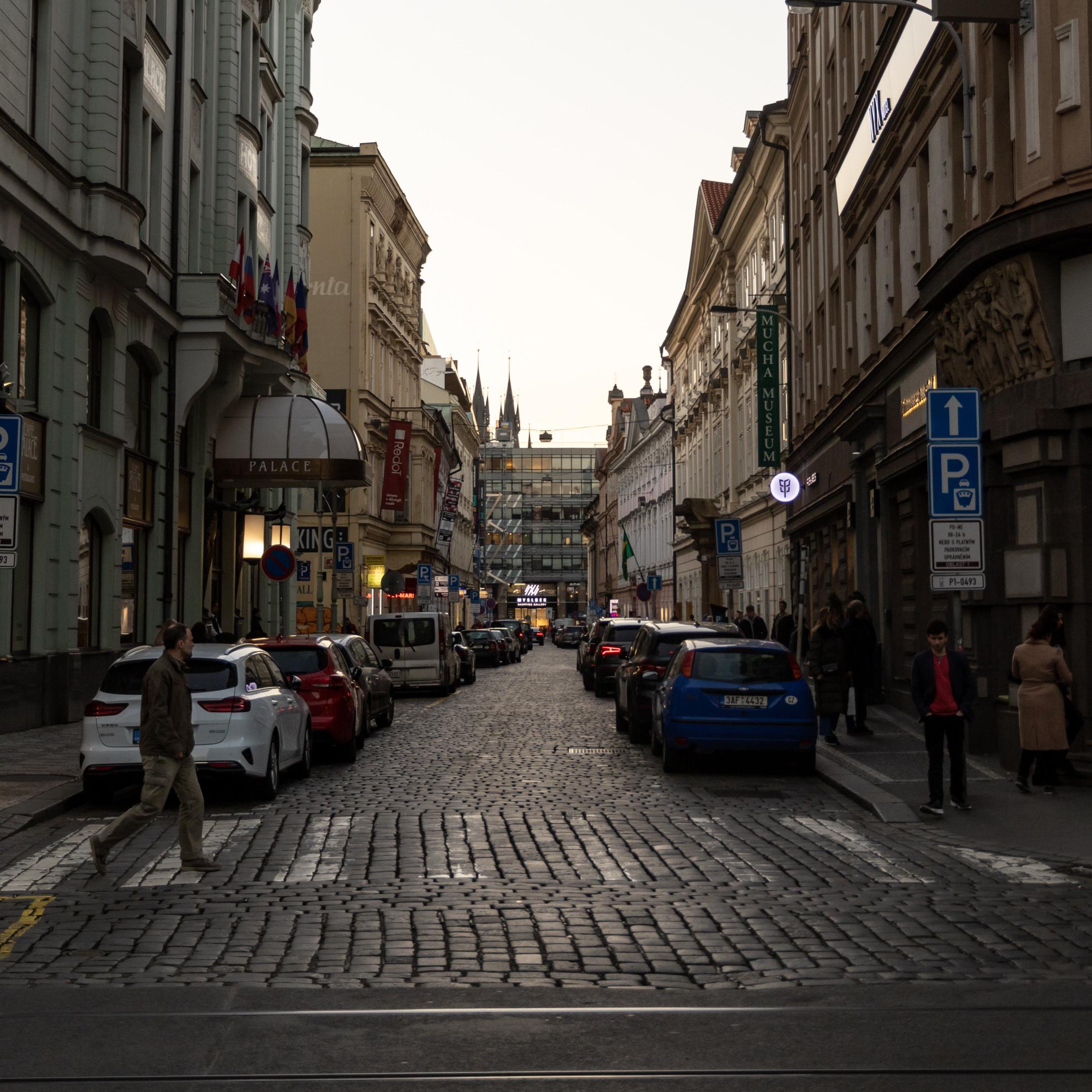 夕方の石畳の通りの様子。高いヨーロッパの建物が通りのを挟む。